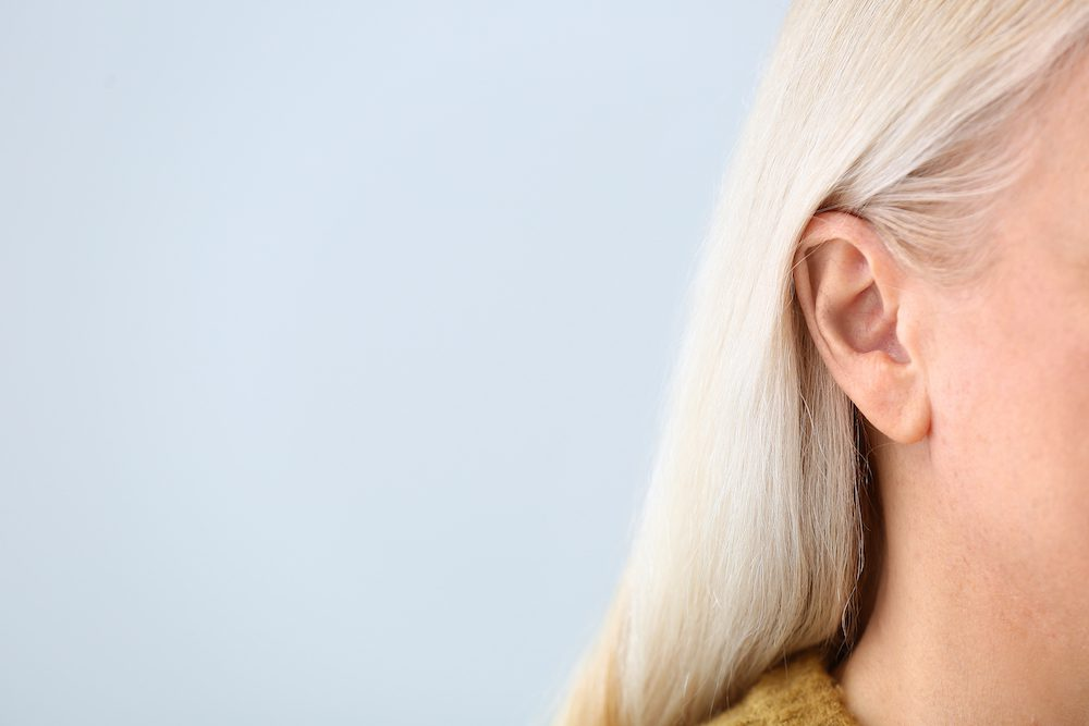 blond woman with hearing loss showing half of face and ear