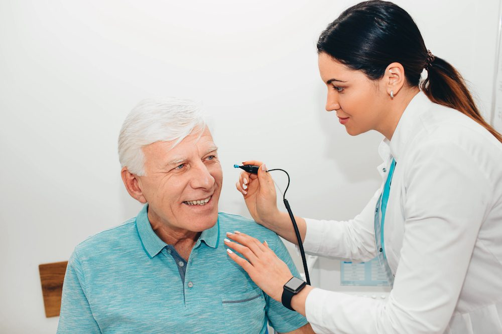 audiologist testing her patient's hearing in office