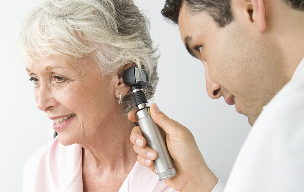 a smiling woman having her ears examined by a hearing doctor
