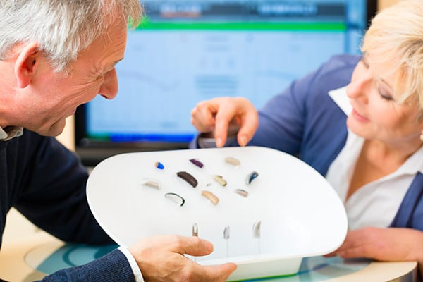 two adults leaning over display of hearing aid devices
