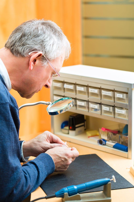 a hearing specialist examining a set of broken hearing instruments