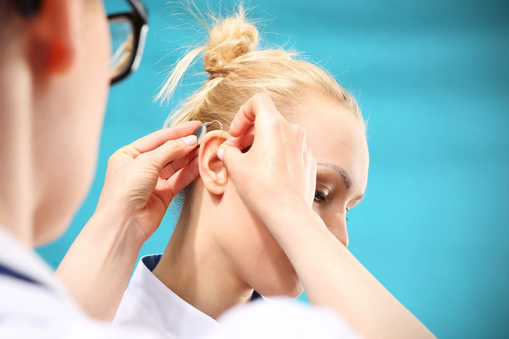 a hearing doctor fitting her patient with new hearing aids