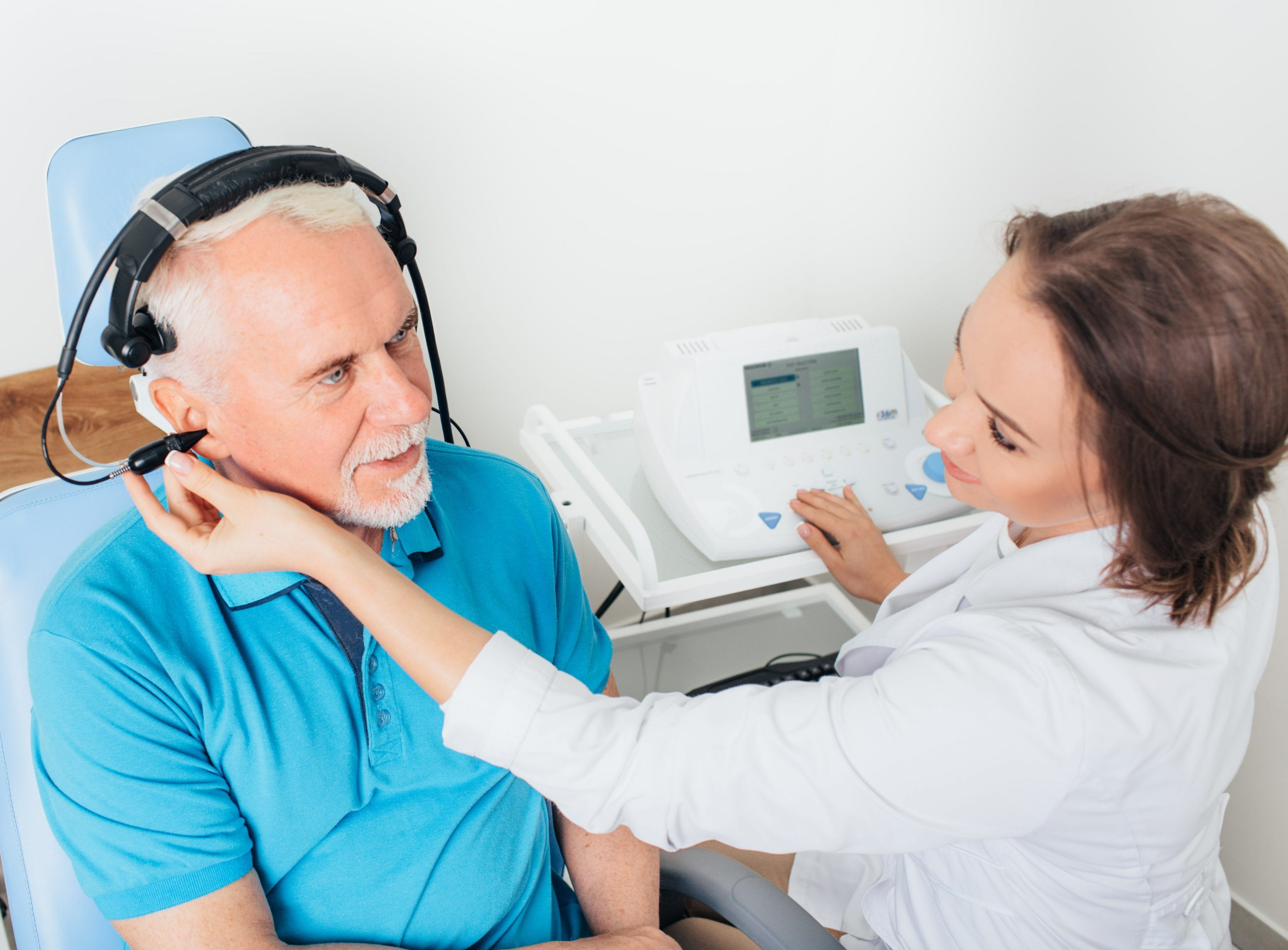 man wearing blue polo shirt having hearing examined by professional audiologist