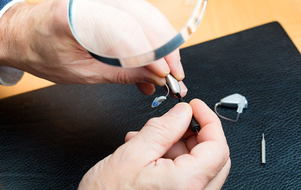 hearing aids being examined under magnifying glass