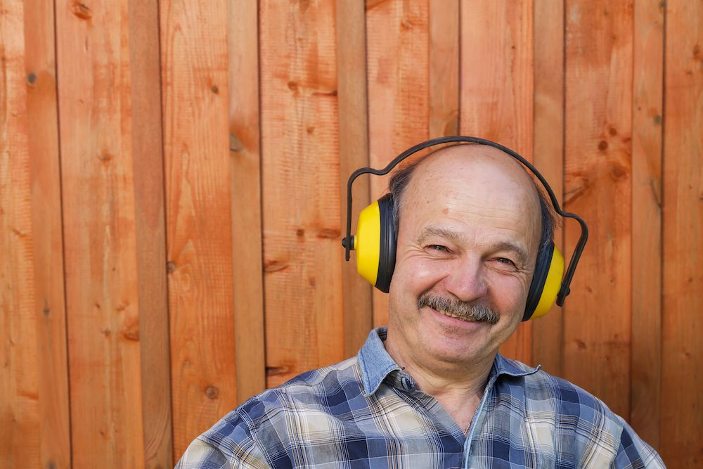 smiling gentleman in plaid shirt is wearing over the head ear protection