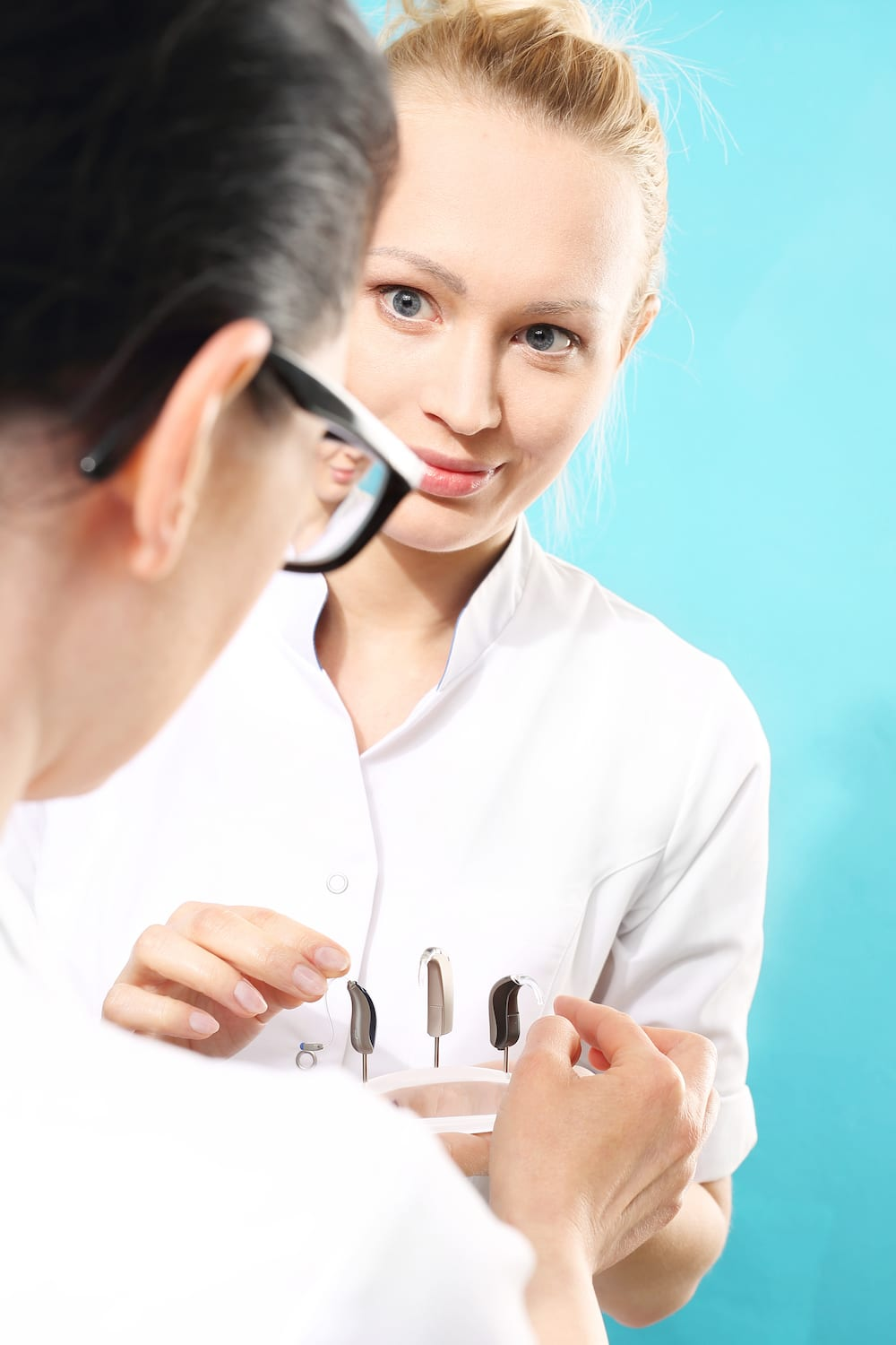 a hearing specialist showing her patient a selection of hearing aids