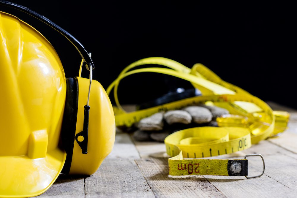 ear protectors next to hard hat and measuring tape