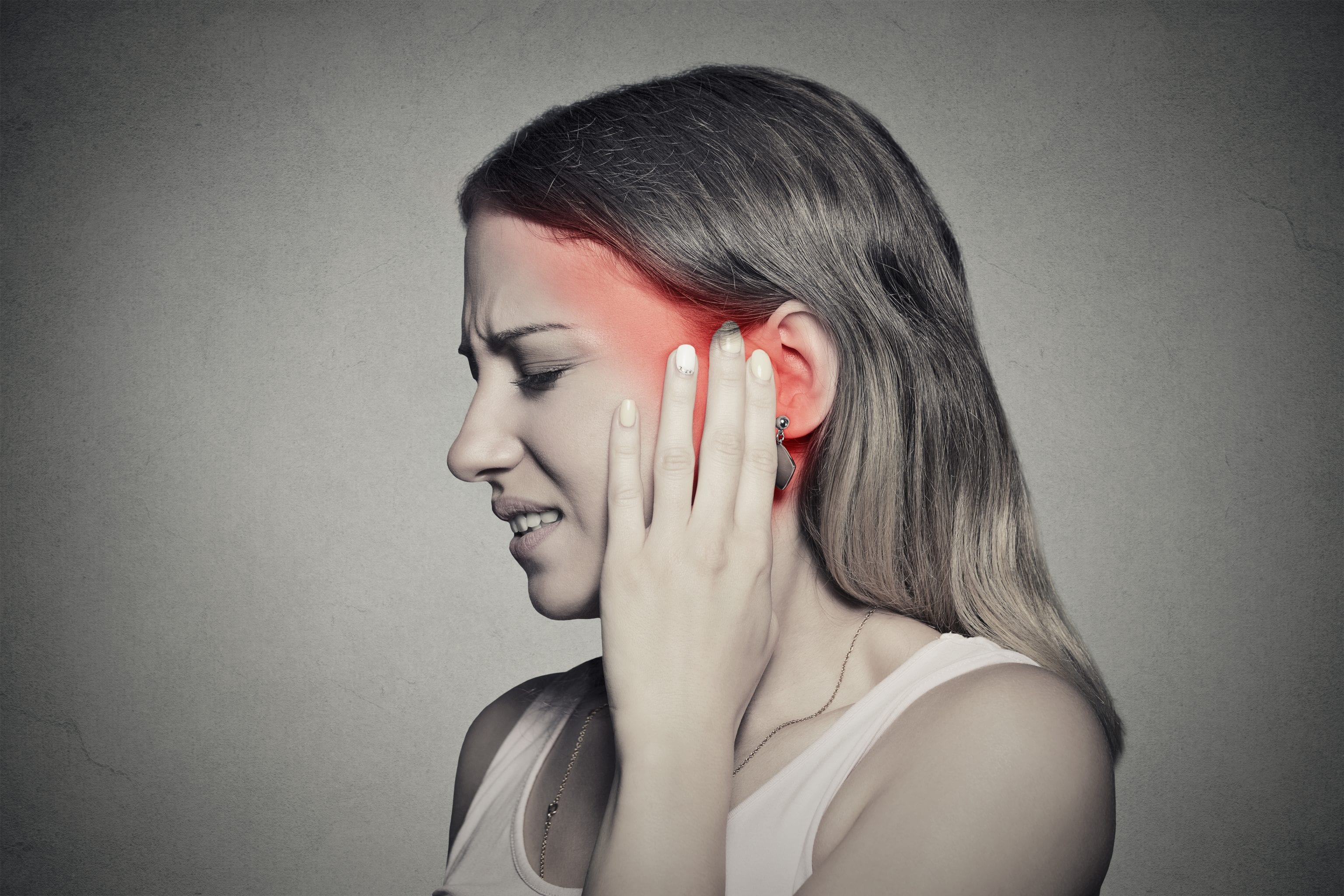 side angle of woman touching ear in distress