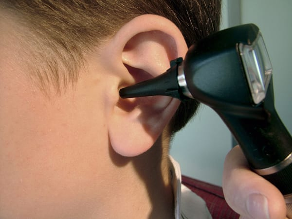 a closeup of a younger child's ear being examined