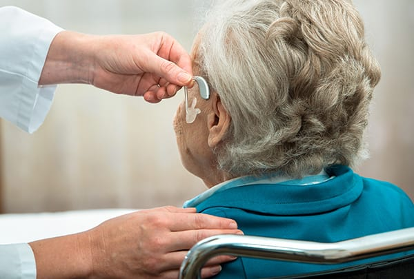 patient with hearing loss sitting during hearing aid fitting appointment