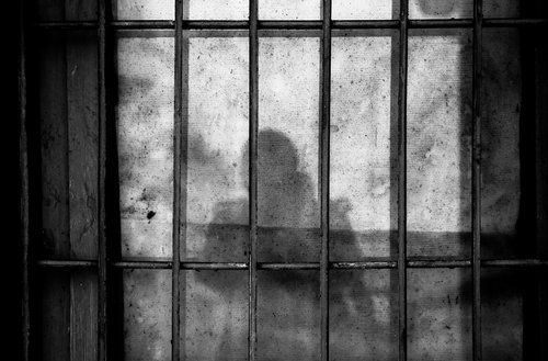 Image of a shadow and a jail cell.