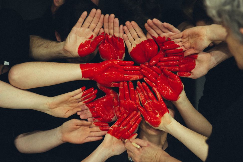 A group of hands with a red heart painted on them.