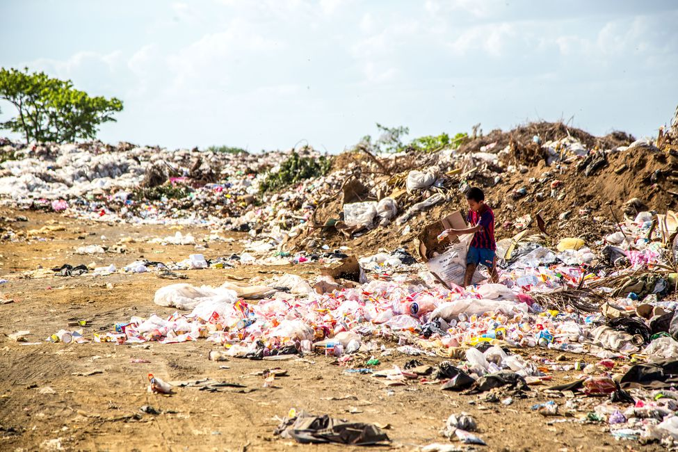 A child stands outside. He is surrounded by a pile of trash in Nicaragua.