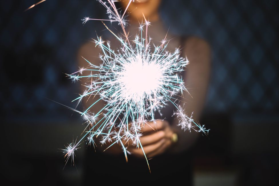 A young woman holds a sparkler.
