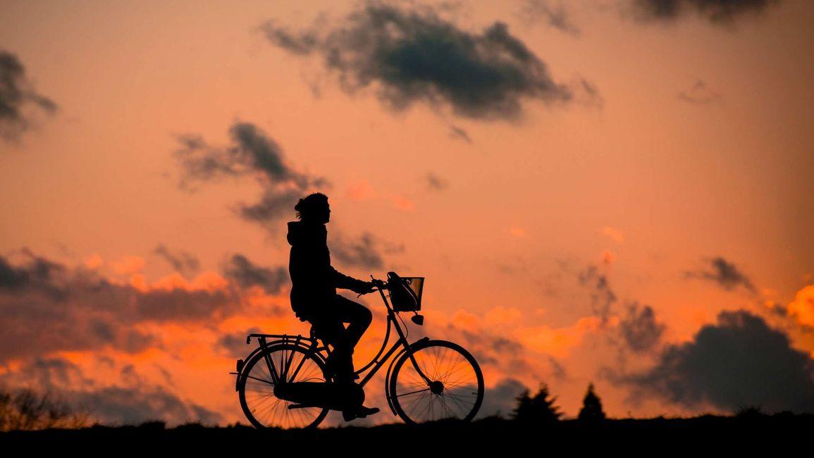 A silhouette of a man biking at sunset.