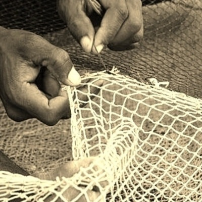 ID: dark skinned hands use a metal hook to mend a white net while other netting is visible in the background.