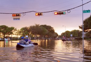 people drive a boat down a flooded street