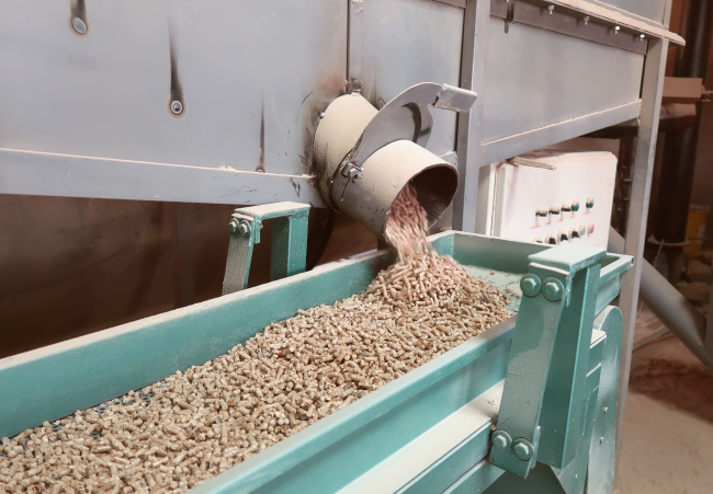 wood pellets emerge from a machine