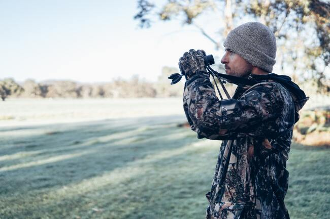 man in camo with binoculars - hunting leases are one way that landowners can make money from their land