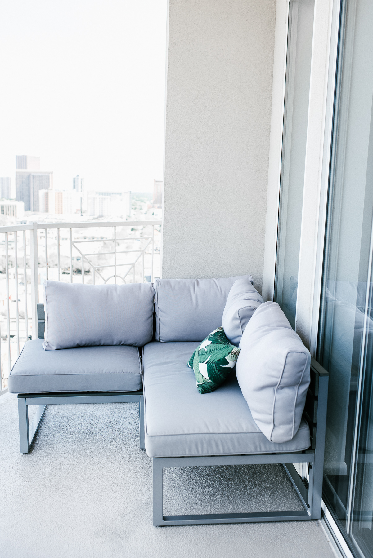Welcome to my Happy Place, Dress Up Buttercup, Dede Raad, Houston Blogger, Fashion blogger, Patio Furniture,Gray outdoor seating, palm leaf pillow, ripped jeans, cute puppy