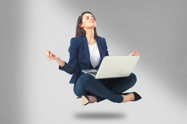 Young businesswoman sitting in yoga lotus position with laptop