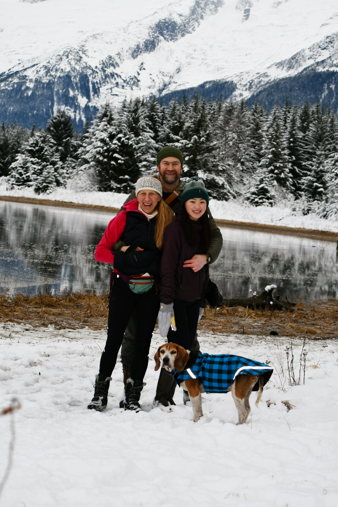Photo of Pete, Sara and Annie Hagen, and a dog, standing in the snow next to Eagle River.