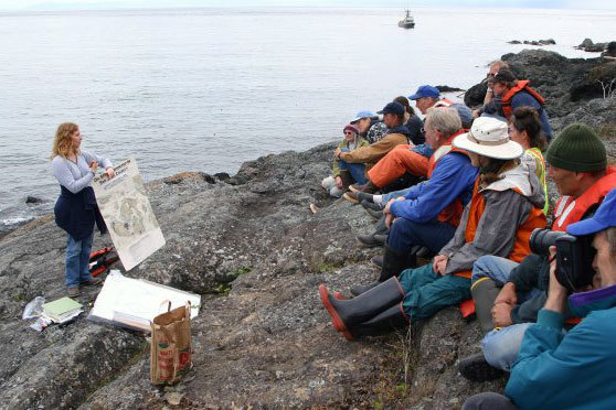Educator giving presentation of people seated outdoors on the coast