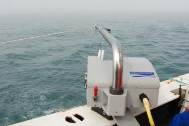 The UCTD unit mounted on a deck rail with a foggy sea in the background