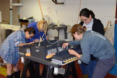 Four female scientists pipette samples out of plastic flow through chambers holding one Atlantic sea scallop each during a biodeposition experiment at the Darling Marine Center in Walpole, Maine.