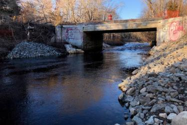 A river passes under a bridge where a  dam once blocked passage.