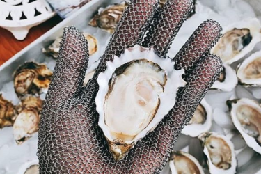 A hand holding an oyster on the half shell.