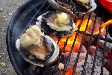 Three abalone on the half shell, topped with garlic and butter, are cooking on a hot grill.