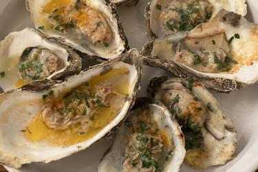 A plate of grilled oysters topped with parsley.