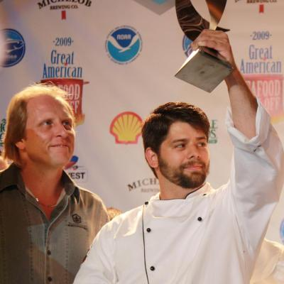 """Peter Fischbach holds up his second place award at the 2009 Great American Seafood Cookoff and stands next to Sigurd Jonny """"Sig"""" Hansen, a commercial fisherman featured in the television series Deadliest Catch."""