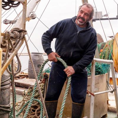 Tony Borges stands on his fishing vessel, holding a rope.