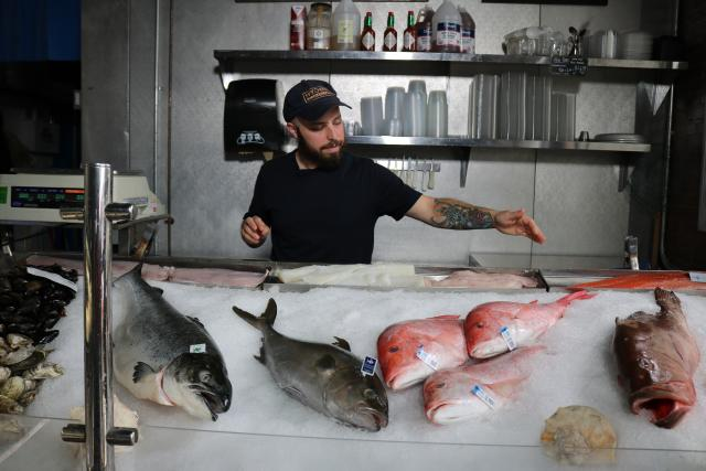 A seafood market employee gestures toward several freshly caught, whole fish laying on a bed of ice next to a kitchen scale for weighing.