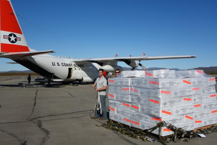 Photo of large US Coast Guard plane and staff on tarmac with delivery of seafood on a pallet.