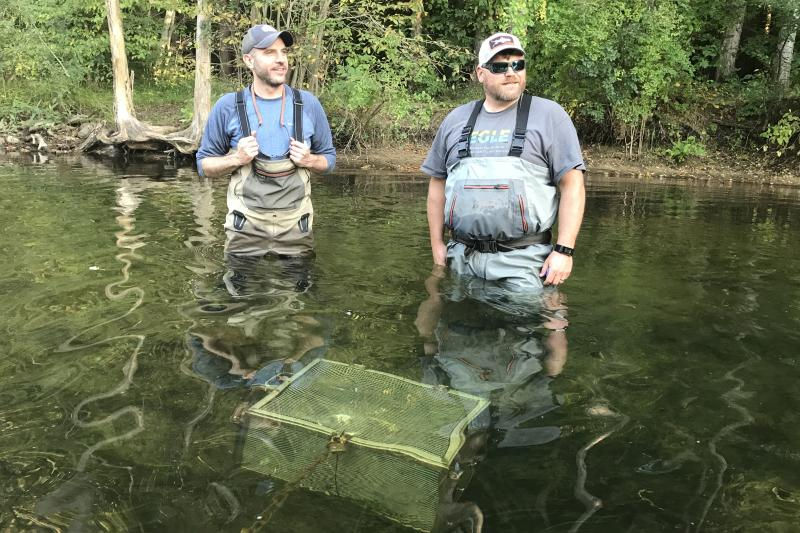 Two scientists stand in a stream, next to water quality testing equipment under the surface.