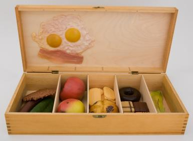 A large, wide wooden box is open, showing five equal sections filled with plastic foods, including vegetables, crackers, cookies, pastries, and a chocolate donut. Two sunny-side up eggs and a slice of bacon are fixed above the inside cover of the box.