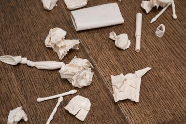 Several white porcelain objects are scattered on a wood floor. Some of the objects are recognizable, such as cotton swabs and crumpled and folded pieces of paper.