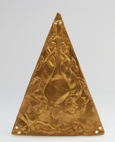 This image shows a luminous, triangular gold plaque with two small round holes drilled in each of the three corners. The long sides of the triangle, which are at the left and right of this image, feature relief images of identical striding tigers with snarling facial features and lean bodies. There is a mythical creature with a human-like head that is joined to two hindquarters, perhaps those of a dog, by a sort of collar on the short side of the triangle, which is the bottom of this image.