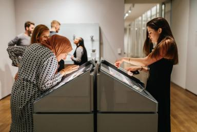In a gallery, a group of three women looks into a lit-up pyramid-shaped display case. Two of them have their hands on a sliding magnifying glass over coins in the case. In the background, three people stand in front of a wall-mounted display case, slightly out of focus.