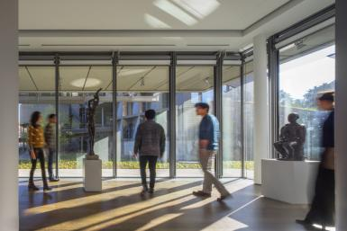 Five people walk around a large gallery that has floor-to-ceiling windows. The figures are slightly blurred. Sunlight floods in, with views to the outside. At the center of the gallery, on a white pedestal, is a bronze sculpture of a person standing with arms raised. To the right is a bronze sculpture of a man seated on a white square pedestal.
