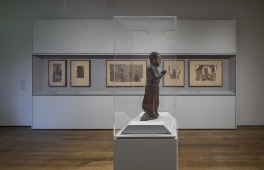 In the center of a gallery is a side view of an enclosed pedestal. The pedestal contains a sculpture of a small child facing right, with a bald head, wearing flowing clothing from the waist down, and with hands clasped together in front of him. In the distance on the far wall, a large case displays various fragments of a cave painting.