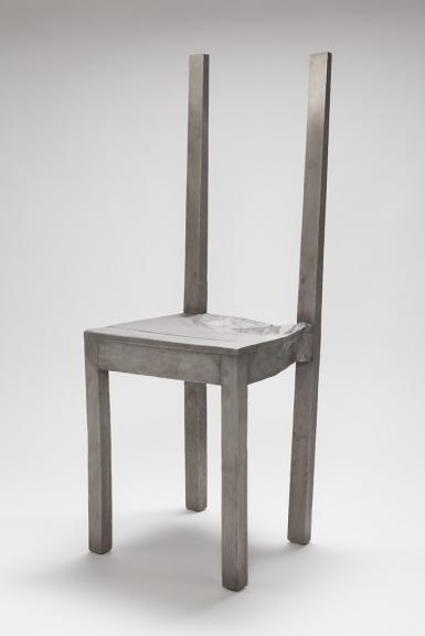 This photograph shows a stainless steel chair with some of its back supports missing. It sits against a white background.