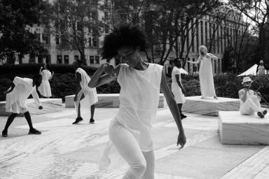 A black and white photo shows several dancers dressed in white on an outdoor marble platform. Each dancer is in various poses around the plaza. The central figure is a Black woman, who is in mid-movement, with her right limbs in a bent position. Her eyes are closed, and her face is directed downward. In the background are hedges, several trees, and buildings.