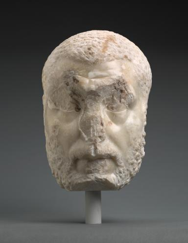 A white marble sculpture depicts the head of a bearded man whose eyes, nose, mouth, and chin are partially destroyed or missing. The man's beard and hair are ornately carved and textured, while his cheeks and forehead are smooth marble.