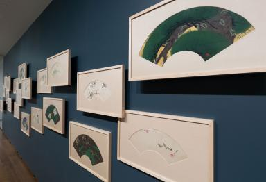 A blue wall in a gallery shows an arrangement of several framed painted fans in an irregular layout. Many of them are spaced off the wall by several inches.