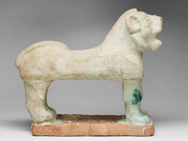 This image shows a small statue of a greenish-white ceramic lion standing on a thin terracotta base. Its four legs are in parallel pairs and the front legs feature patches of green. Its tail is tucked flat against its back and its mouth is open, as if roaring.
