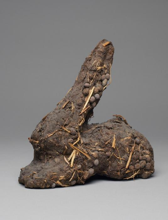 This molded sculpture depicts a small rabbit lying down with ears extended and front limbs outstretched in near profile view. Small, spherical shapes and bits of yellow can be seen throughout the sculpture, giving it a roughly textured surface.
